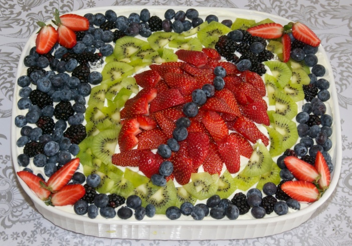 Whipped cream and fresh fruit for a bug-themed birthday cake by Jewels at Home.