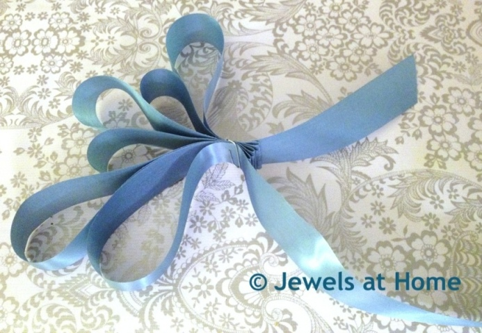 Gather some ribbon and secure it with a paperclip for decorating your diaper cake.