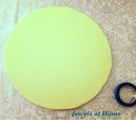 Wrap the cardboard circle in fabric or paper and secure it on the bottom with tape.