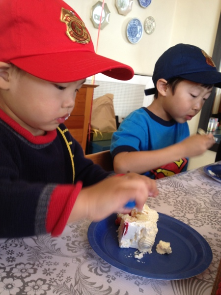 Birthday boy and his brother enjoying cake and their new firefighter caps.