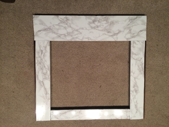 Faux marble contact paper instantly transforms a boring fireplace | Jewels at Home